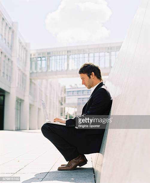 Businessman Leaning Against a Wall Using Laptop