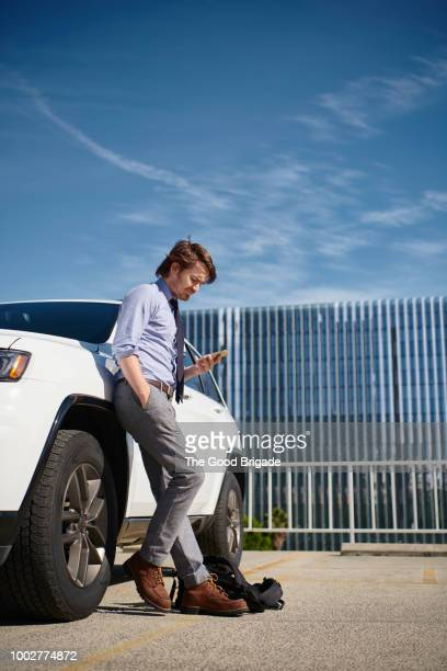 businessman leaning against car looking at mobile phone - lehnend stock-fotos und bilder