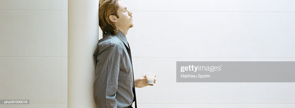 Businessman leaning against column, holding cup of coffee, side view, panoramic : Stockfoto
