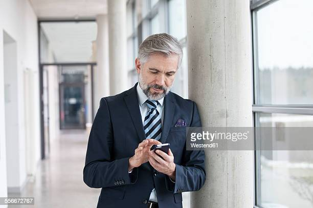 Businessman leaning against column using smartphone