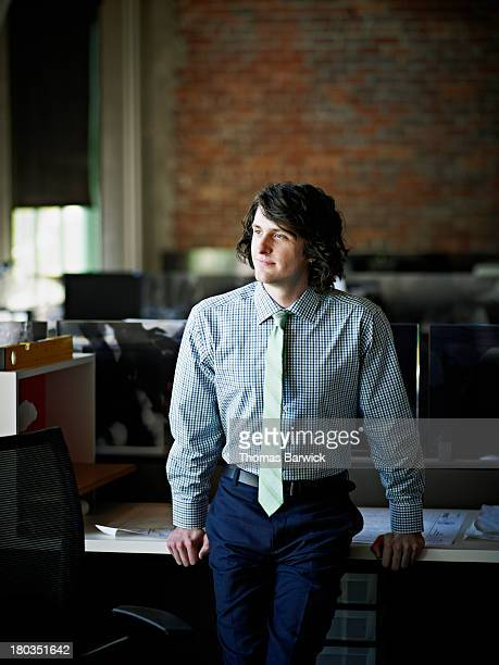 Businessman leaning against desk in office