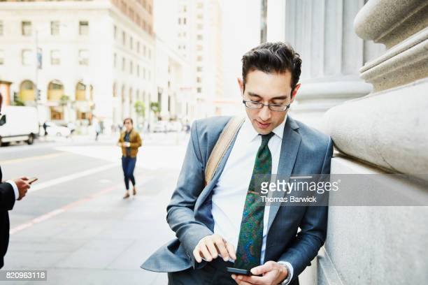 Businessman leaning against downtown building while working on smartphone