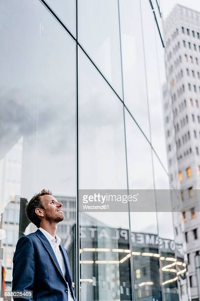 Businessman leaning against glass facade