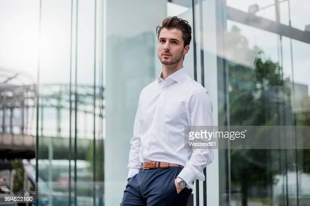 businessman leaning against glass facade - シャツ ストックフォトと画像
