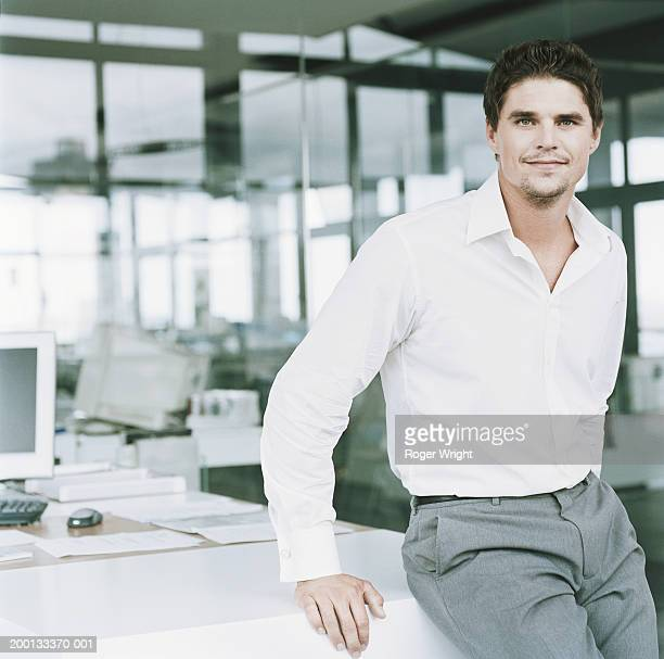 businessman leaning against office desk, portrait - open collar stock pictures, royalty-free photos & images
