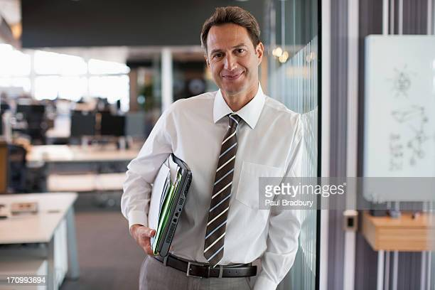 Businessman leaning against office wall
