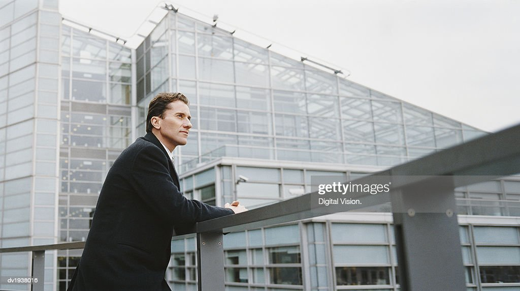 Businessman Leaning Against the Railing of a Building and Looking at the View : Stock Photo