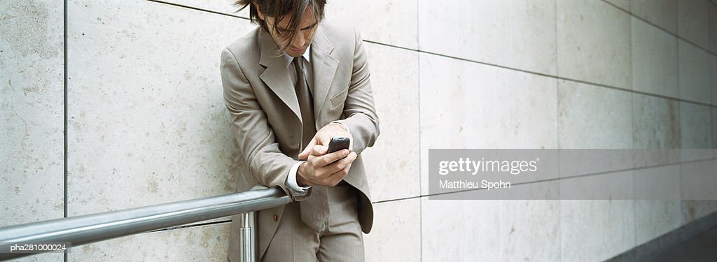 Businessman leaning against wall and handrail, looking at cell phone, panoramic : Stockfoto