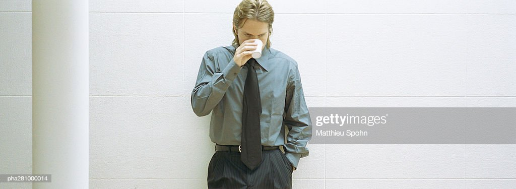 Businessman leaning against wall, drinking coffee, panoramic : Stockfoto