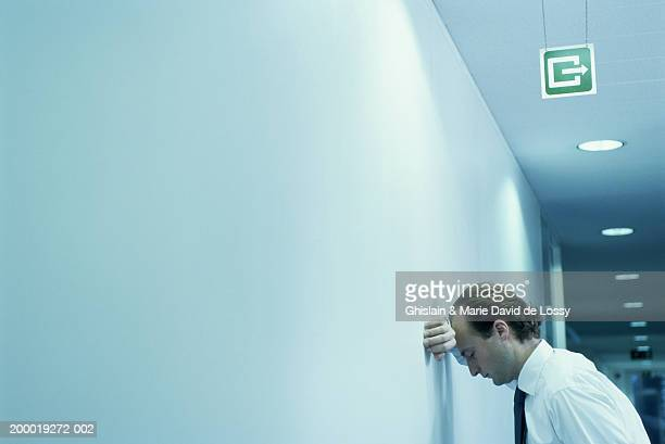 Businessman leaning against wall in corridor