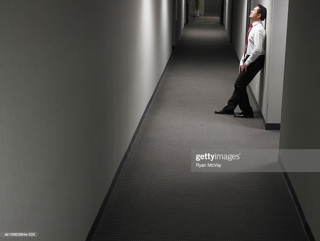 Businessman Leaning Against Wall In Dark Hallway, Side View : Stock Photo