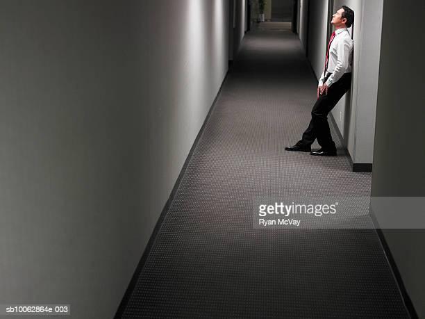Businessman leaning against wall in dark hallway, side view