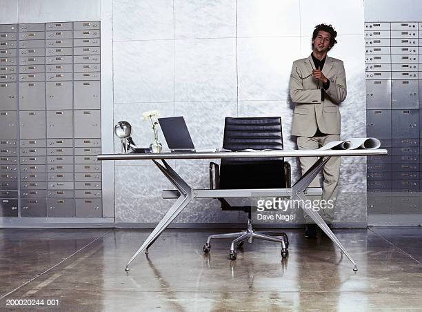 Businessman leaning against wall in vault, portrait