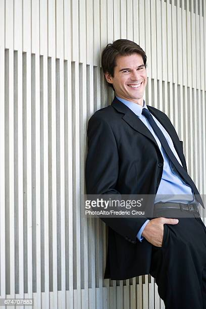 Businessman leaning against wall with hands in pockets, smiling cheerfully