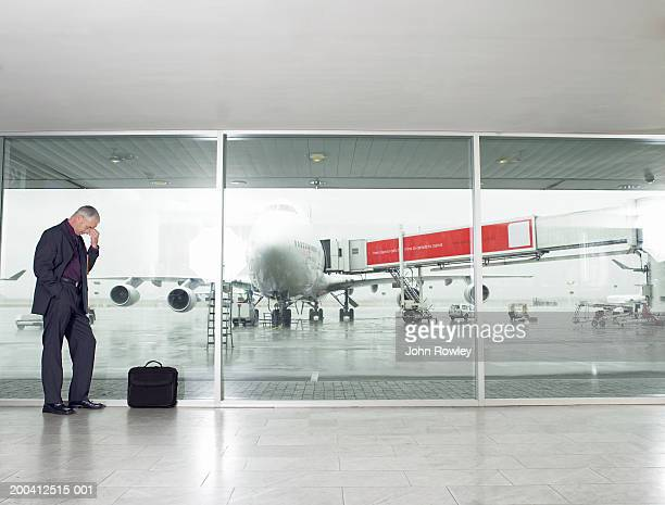 Businessman leaning against window in airport, pinching bridge of nose, eyes closed