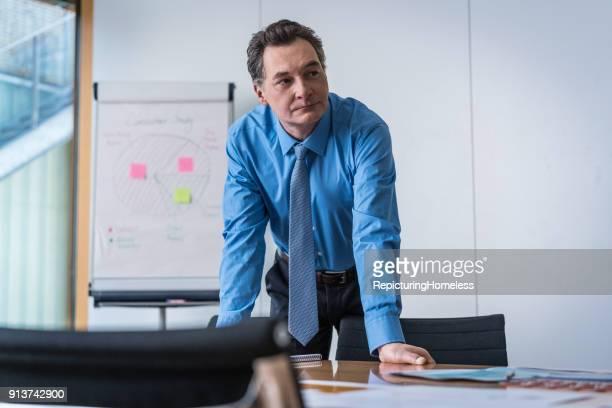Ein Geschäftsmann lehnt auf einem Tisch und schaut zur Seite