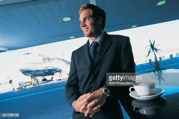 Businessman Leaning at an Airport Bar Counter With a Coffee