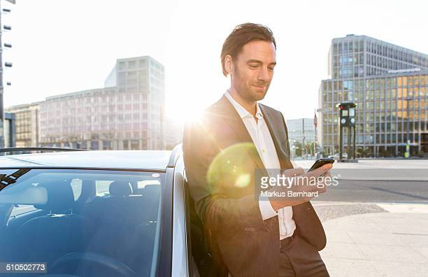 Businessman leaning at car and texting with mobile