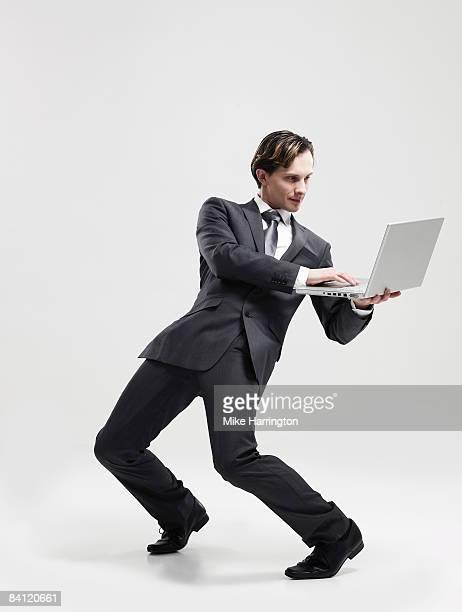 Businessman leaning back holding laptop