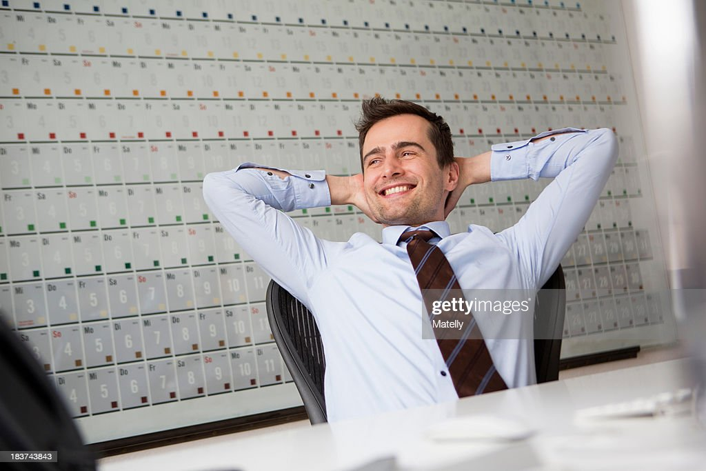 Businessman leaning back in chair with arms behind head : Stock Photo