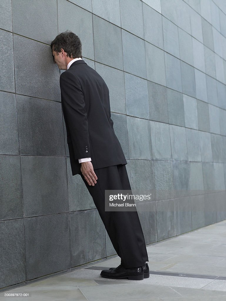 Businessman leaning forward, resting face against wall, side view : Stock Photo
