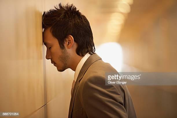 businessman leaning his head against a wall - oliver eltinger stock-fotos und bilder