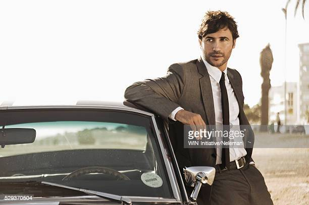 Businessman leaning on a car