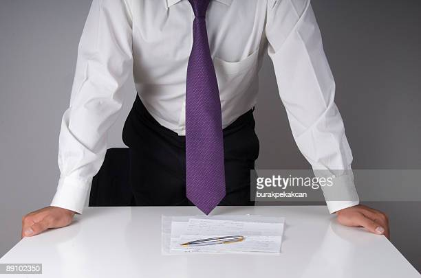businessman leaning on a conference table - purple shirt stock photos and pictures