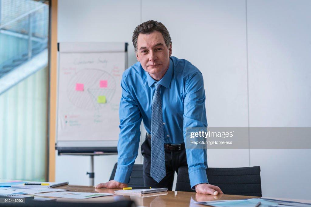 Ein Geschäftsmann lehnt auf einem Tisch und schaut in die Kamera : Stock-Foto