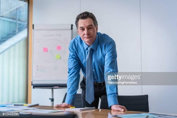 Ein Geschäftsmann lehnt auf einem Tisch und schaut in die Kamera