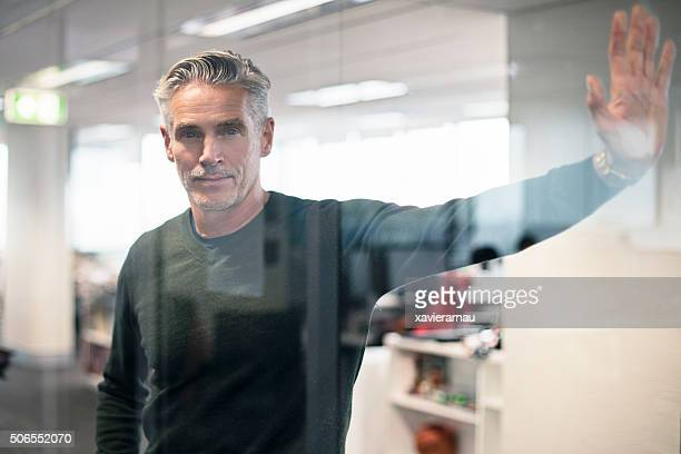 Businessman leaning on a glass in the office