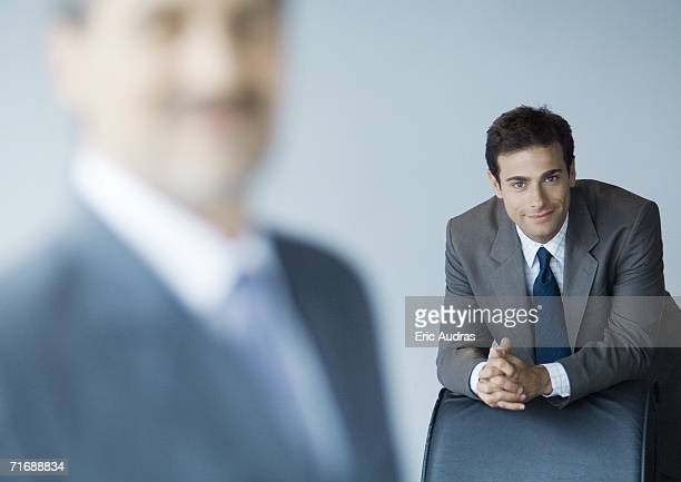 Businessman leaning on back of chair, focus on background