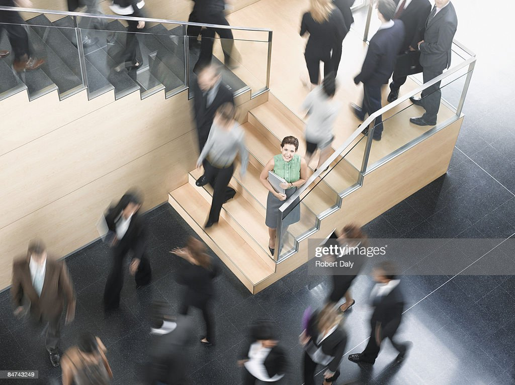 Businessman leaning on busy office staircase : Stock Photo