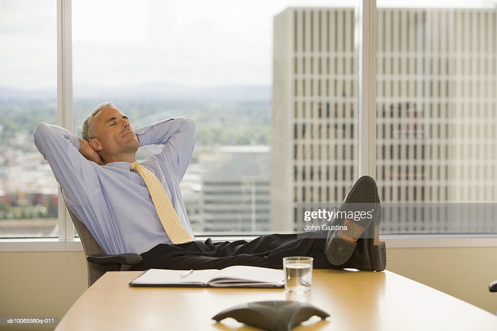 Businessman leaning on chair with hands behind head, eyes closed : Foto stock