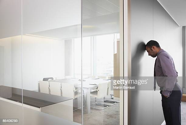 Businessman leaning on corridor wall