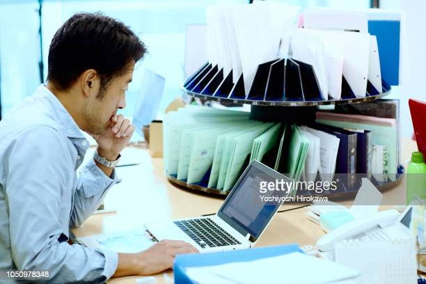 Businessman leaning on desk in office of high tech startup working on computer