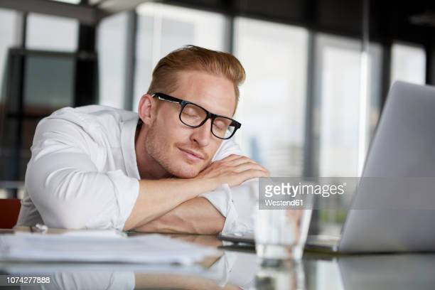 businessman leaning on desk in office with closed eyes - sonnecchiare foto e immagini stock