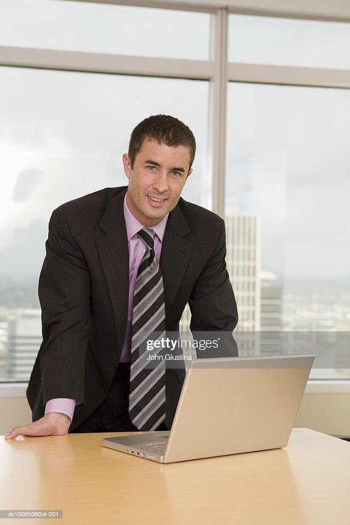 Businessman leaning on desk, portrait : Foto stock