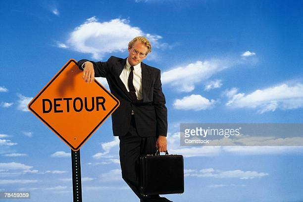 businessman leaning on detour sign - detour sign stock photos and pictures