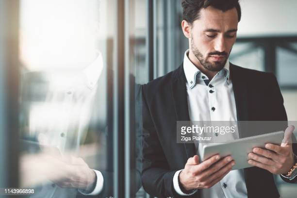 businessman leaning on the window in his office working on a digital tablet - speech stock pictures, royalty-free photos & images