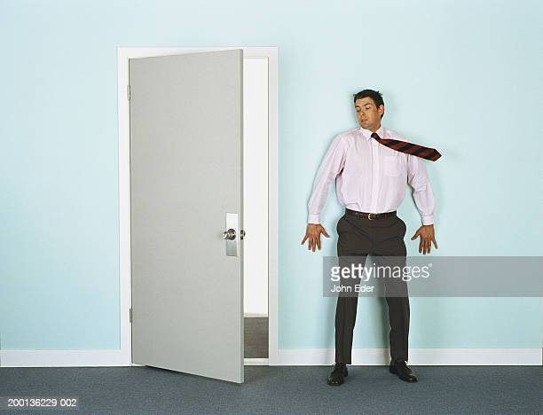 Businessman leaning on wall by doorway, tie blowing in wind