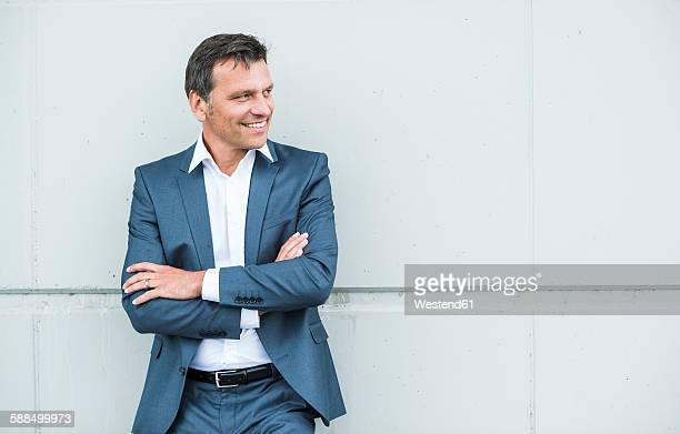 Businessman leaning on wall with arms crossed