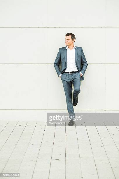 Businessman leaning on wall with hands in pockets