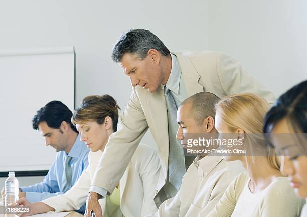 Businessman leaning over colleague's shoulder during meeting