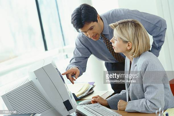 Businessman leaning over female colleague's shoulder pointing at monitor