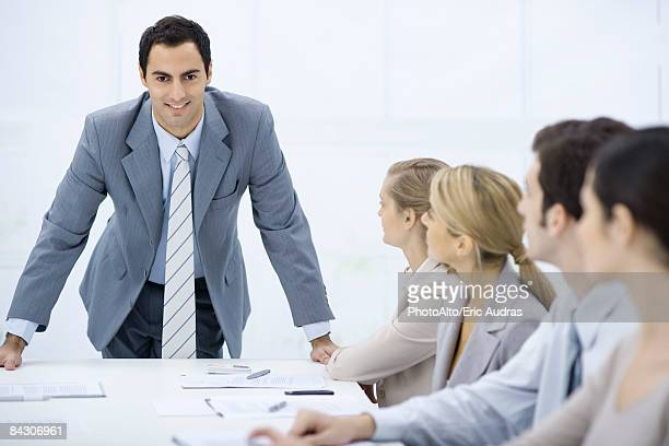 Businessman leaning over table addressing colleagues, smiling at camera