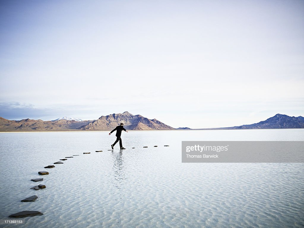Businessman leaping between stones on pathway in l : Stock Photo