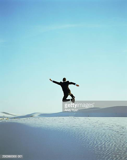 businessman leaping, clicking heels in desert, rear view - 日常から抜け出す ストックフォトと画像