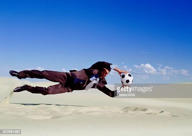 Businessman Leaping for Soccer Ball