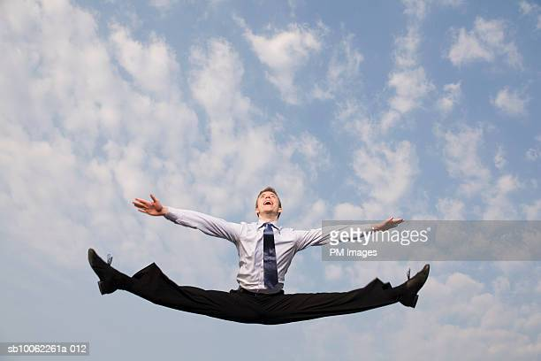 Businessman leaping with arms outstretched, against sky
